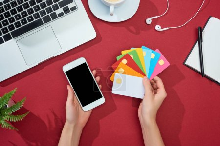 Photo for Cropped view of woman holding multicolored empty credit cards and smartphone on red background with laptop, earphones and coffee - Royalty Free Image