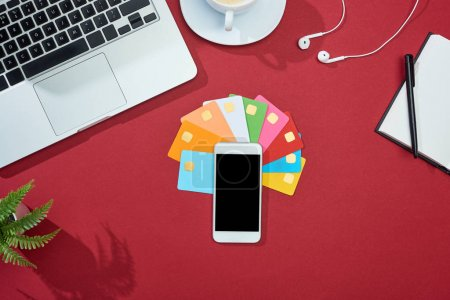Photo for Top view of multicolored empty credit cards on red background with smartphone, laptop, earphones and coffee - Royalty Free Image
