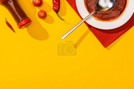 Photo for Top view of chili peppers with cherry tomatoes, plate and bottle with ketchup on yellow surface - Royalty Free Image