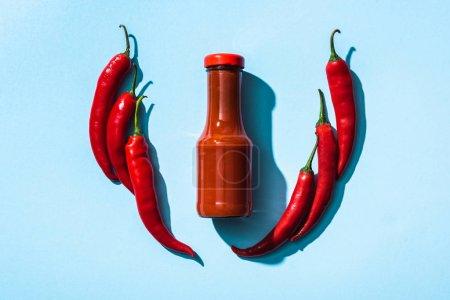 Photo pour Vue du dessus de la sauce chili en bouteille entre les piments sur fond bleu - image libre de droit