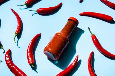 Photo for Bottle with tasty chili sauce and chili peppers on blue background - Royalty Free Image