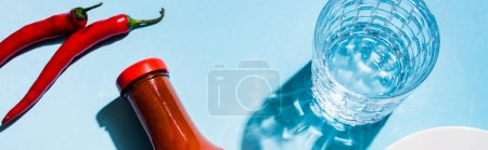 Top view of glass of water with chili sauce and chili peppers on blue background, panoramic shot