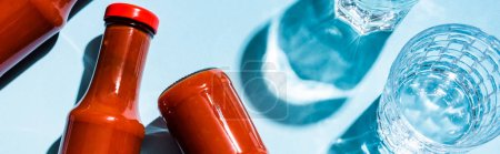 Top view of bottles with tasty ketchup beside glasses of water on blue background, panoramic shot