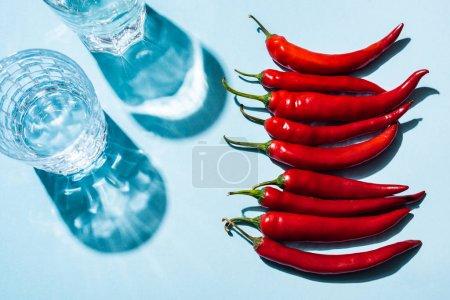 Photo pour Vue en haut des piments chili frais à côté des verres d'eau sur fond bleu - image libre de droit