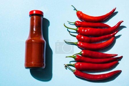 Photo pour Vue du dessus de la sauce chili et des piments mûrs à la surface bleue - image libre de droit