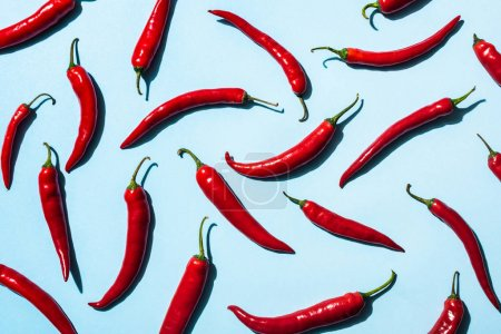 Photo for Top view of red chili peppers on blue background - Royalty Free Image