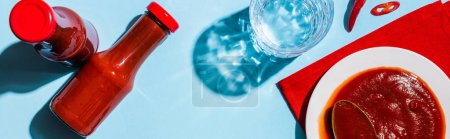 Top view of ketchup in plate and bottles beside chili pepper and glass of water on blue surface, panoramic shot