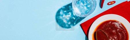 Photo pour Vue du dessus de la sauce chili sur une assiette à côté du verre d'eau et du piment sur une surface bleue, vue panoramique - image libre de droit