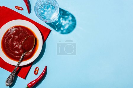 Delicious chili sauce in pate on red napkin beside glass of water and chili peppers on blue surface