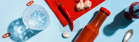 Photo for Top view of bottles with ketchup, garlic with chili pepper and glass of water on blue sutface, panoramic shot - Royalty Free Image