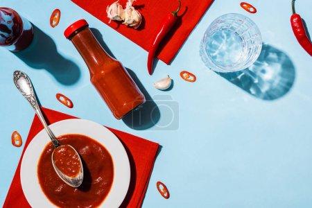 Photo pour Vue du dessus de ketchup savoureux à l'ail, piments épicés et verre d'eau sur fond bleu - image libre de droit