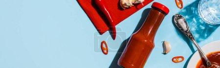 Horní pohled na rajčatovou omáčku s chilli paprikou a sklenicí vody na modrém povrchu, panoramatický záběr