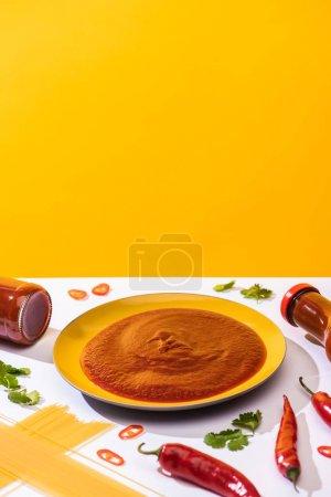 hausgemachte würzige Tomatensauce mit Spaghetti und Chilischoten auf weißer Oberfläche auf gelbem Hintergrund