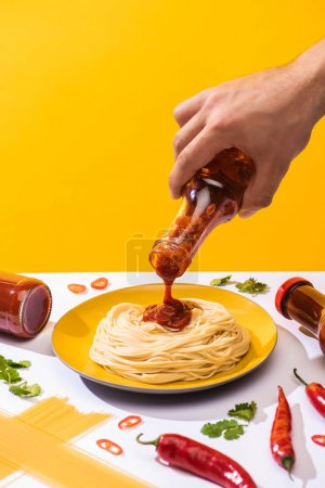 Photo for Cropped view of man pouring ketchup on spaghetti with chili peppers and greenery on white surface isolated on yellow - Royalty Free Image