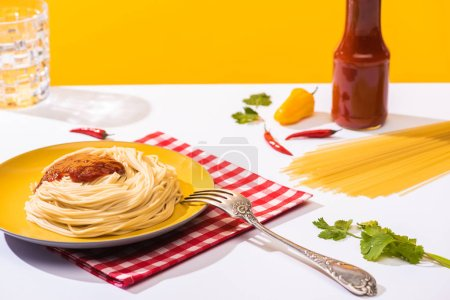 Photo for Selective focus of homemade spaghetti with ketchup, cilantro and peppers on white surface on yellow background - Royalty Free Image