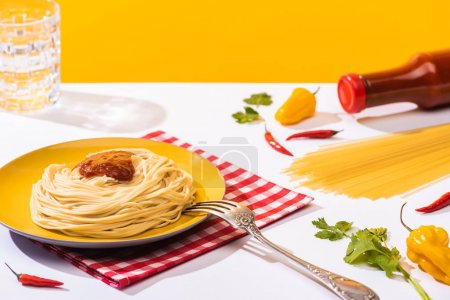 Tasty spaghetti with ketchup beside peppers and glass of water on white surface on yellow background