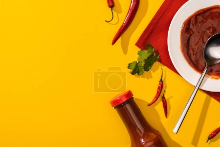 Photo for Top view of tomato sauce with hot chili peppers and cilantro on yellow background - Royalty Free Image