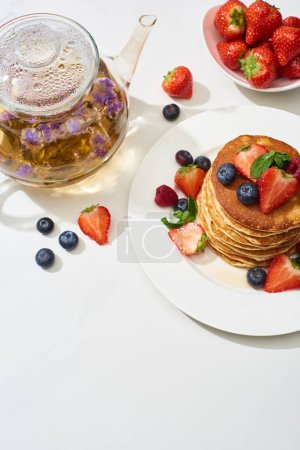 Photo for Top view of delicious pancakes with maple syrup, blueberries and strawberries on plate near herbal tea in teapot on marble white surface - Royalty Free Image