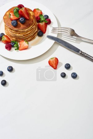 Photo for Top view of delicious pancakes with maple syrup, blueberries and strawberries on plate near fork and knife on marble white surface - Royalty Free Image