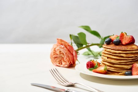 Photo for Selective focus of delicious pancakes with blueberries and strawberries on plate near rose flower and cutlery on white surface isolated on grey - Royalty Free Image