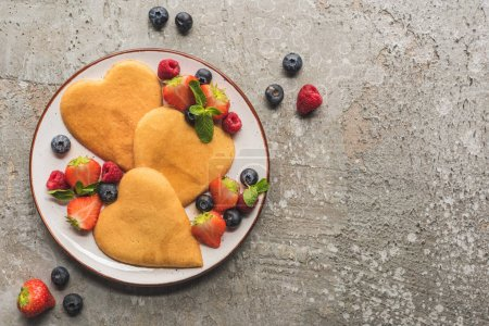 Photo for Top view of heart shaped pancakes with berries on grey concrete surface - Royalty Free Image