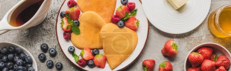 Photo for Top view of heart shaped pancakes with berries on grey concrete surface with butter, honey and maple syrup, panoramic shot - Royalty Free Image