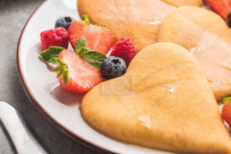 Photo pour Vue de près de délicieuses crêpes en forme de coeur avec des petits fruits dans l'assiette - image libre de droit