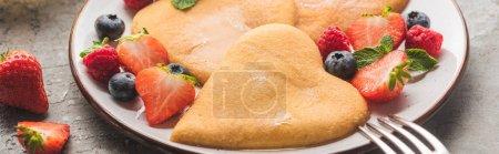 leckere herzförmige Pfannkuchen mit Beeren auf Teller mit Gabel auf grauer Betonoberfläche, Panoramaaufnahme
