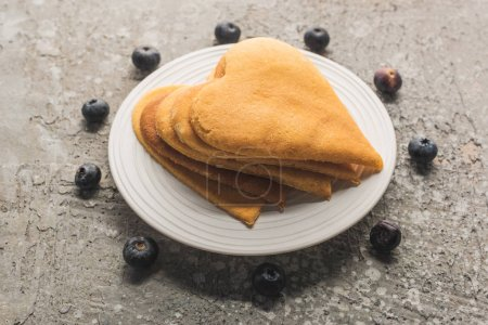 delicious heart shaped pancakes on plate near blueberries on grey concrete surface