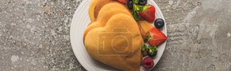 top view of heart shaped pancakes with berries on grey concrete surface, panoramic shot