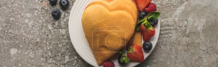 top view of heart shaped pancakes with tasty berries on plate on grey concrete surface, panoramic shot