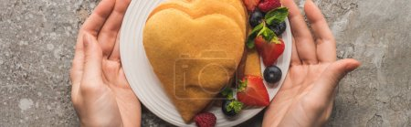 Photo for Partial view of woman holding plate with heart shaped pancakes and tasty berries on grey concrete surface, panoramic shot - Royalty Free Image