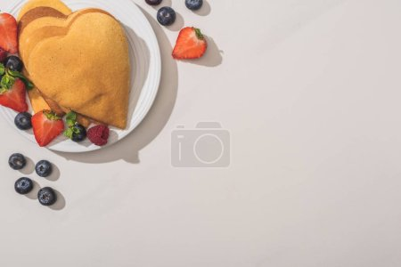 Photo for Top view of heart shaped pancakes with tasty berries on plate on white background - Royalty Free Image
