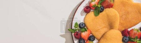 Draufsicht auf leckere herzförmige Pfannkuchen mit Beeren und Minze auf weißem Hintergrund, Panoramaaufnahme