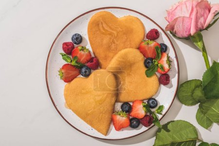 Photo for Top view of delicious heart shaped pancakes with berries near rose on white background - Royalty Free Image