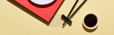 Photo pour Top view of fresh nigiri with salmon near soy sauce and chopsticks on red and beige surface, panoramic shot - image libre de droit