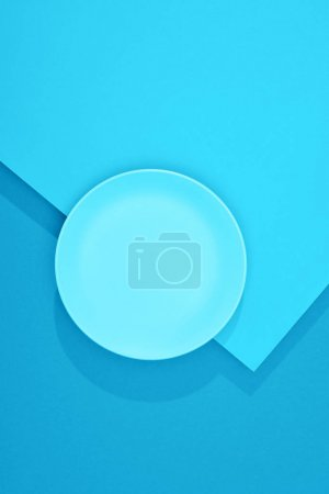 Photo for Top view of empty plate on colorful blue surface - Royalty Free Image