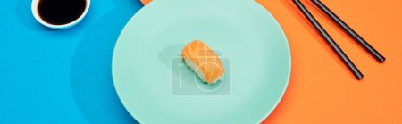 Photo for Fresh nigiri with salmon near soy sauce and chopsticks on blue and orange surface, panoramic shot - Royalty Free Image