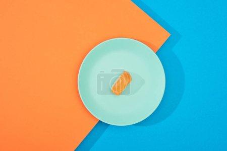 Photo pour Top vue de nigiri frais avec saumon sur surface bleue et orange - image libre de droit