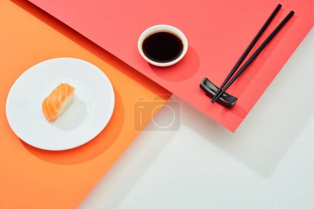 Photo for Fresh nigiri with salmon near soy sauce and chopsticks on red, orange, white surface - Royalty Free Image