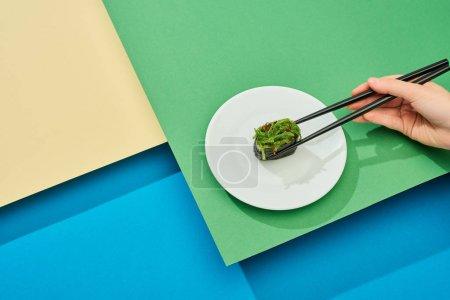 Photo pour Vue en coupe d'une femme mangeant des nigiri frais avec des algues et des baguettes sur une surface multicolore - image libre de droit