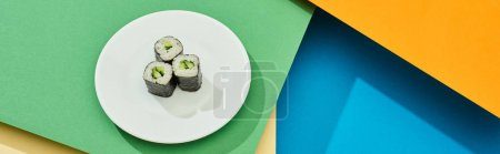 Photo for Fresh maki with cucumber on plate on multicolored surface, panoramic shot - Royalty Free Image