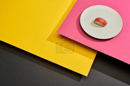 Photo pour Nigiri frais avec thon en assiette sur surface noire, rose et jaune - image libre de droit