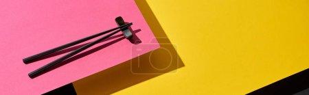 chopsticks on pink, yellow and black surface, panoramic shot