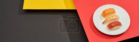 Photo for Fresh nigiri with salmon, shrimp and tuna on red, yellow and black surface, panoramic shot - Royalty Free Image