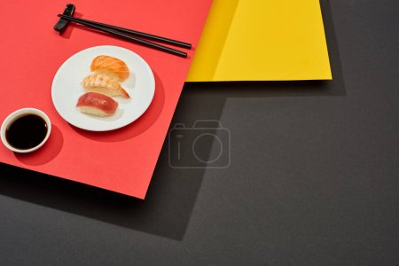 Photo for Fresh nigiri with salmon, shrimp and tuna near soy sauce and chopsticks on red, yellow and black surface - Royalty Free Image