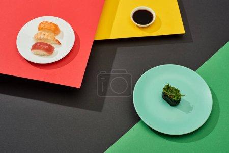 fresh nigiri with salmon, shrimp and tuna near soy sauce and nigiri with seaweed on red, yellow, green and black surface
