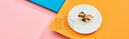 Photo for Fresh nigiri with eel on plate on blue, pink, orange surface, panoramic shot - Royalty Free Image