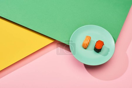 Photo for Fresh nigiri with salmon and red caviar on yellow, pink, green background - Royalty Free Image