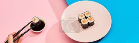 Photo for Cropped view of woman eating fresh maki with salmon near soy sauce on blue, pink background, panoramic shot - Royalty Free Image